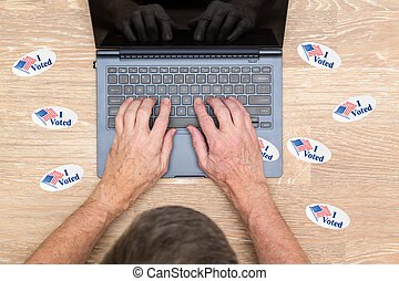 Many I Voted stickers on desk of hacker