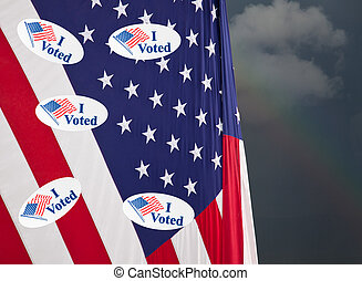 Many I Voted stickers on stars and stripes USA flag