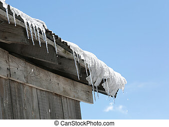 many ice icicles on the roof that melt