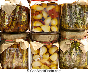 many jars with garlic cloves with peppers and marinated...