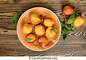 Many juicy beautiful amazing nice peaches on dark wooden background.