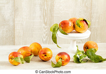 Many juicy beautiful amazing nice peaches on light wooden...