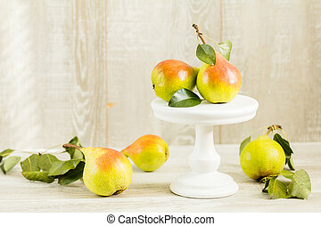 Many juicy beautiful amazing nice pears on light wooden...