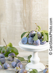 Many juicy beautiful amazing nice plums on light wooden...