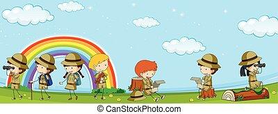Many kids in scout uniform having fun in park