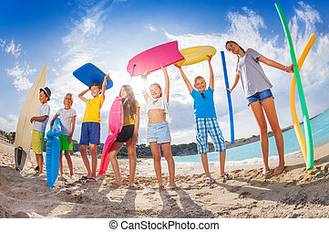 Many kids on a beach with swimming tools and toys