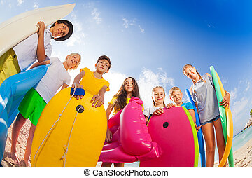 Many kids on beach with swimming stuff