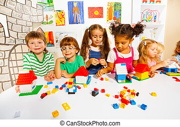 Many kids play with plastic blocks in classroom - Large ...