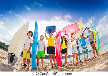 Many kids with mattresses surf boards on the beach