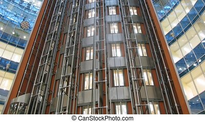 Many lifts move downwards and upwards in business center,...