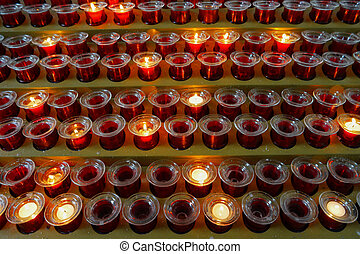 Many lighted candles in candlesticks. Sacred light