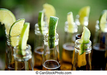 Many limes and many beers - Close up image of multiple beer ...