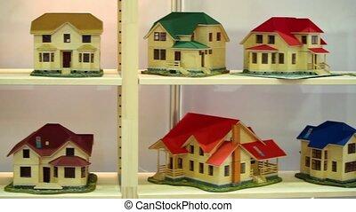 Many models of houses on wooden shelves, shown in motion