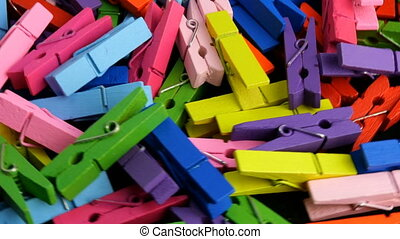 Many multi colored wooden clothespins in heap rotate in circle. Colorful background.