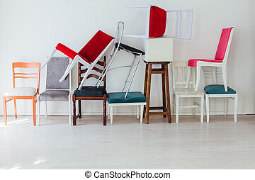 many multicolored chairs stand in the white room