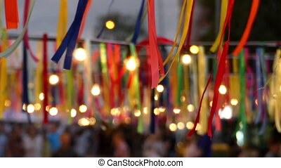 Many multicolored stripes with lamps hanging on the street in summer