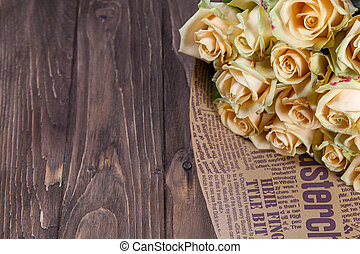 Many natural beige roses background on a wooden table
