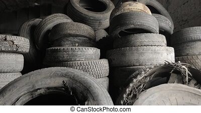 Many old rubber car tires in shop of processing recycling plant. Landfill of used automobile wheel tyres. Seasonal car tire replacement. Environmental protection, recycling of used materials.
