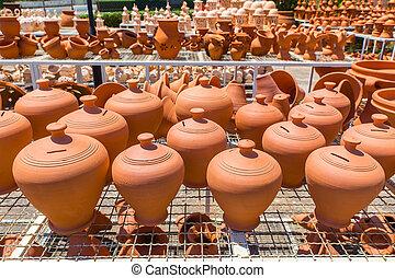 Many orange clay pots outside at pottery