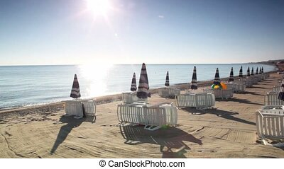 Many parasols and deckchairs standing on beach at sunny day,...