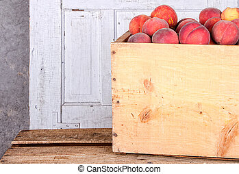 Many peaches in wooden crate