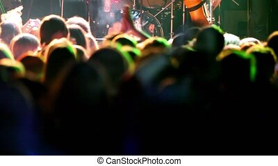 Many people applaud on concert, view from behind