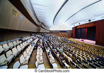 many people are sitting in easy chairs in big conference hall