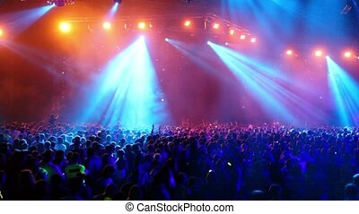 Many people at rave party, crowd dance in blue light of...