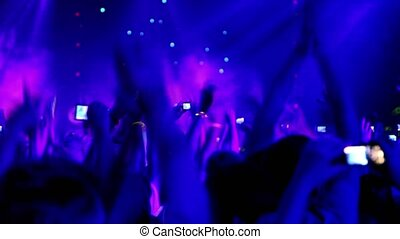 Many people at rave party, view from behind