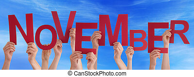 Many People Hands Holding Red Word November Blue Sky