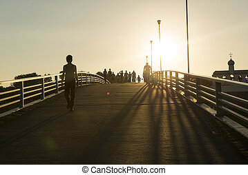 many people, men and women go over the bridge in the rays of the setting sun