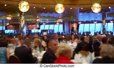 Many people sit at tables in restaurant on ship during cruise