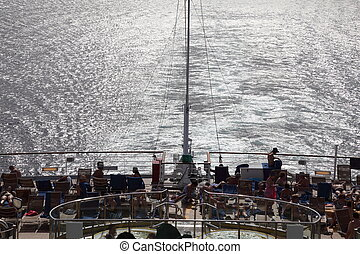 many people sitting and standing on deck of cruise ship.