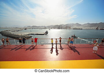 many people standing on deck of cruise ship. ships far away