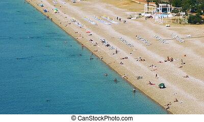 Many people sunbathing on the Konyaalti beach in Antalya and bathing in the Mediterranean sea