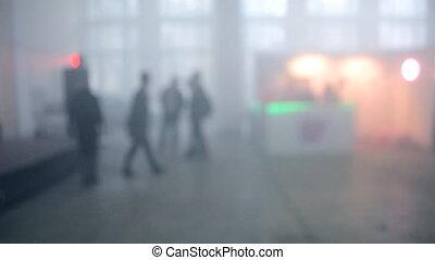 Many people walk in a smoke filled room - Many people walk...