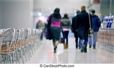 Many people walk in cafe, empty chairs stand on both side
