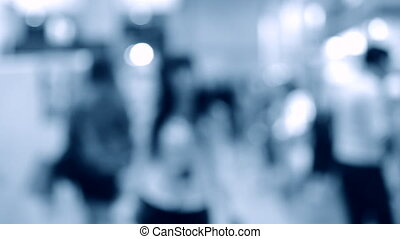 Many people walk inside the mall exhibition store. Blurred ...