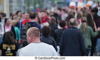 Many people walking along street in city
