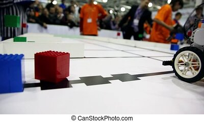 Many people watch on robot moves and take cube
