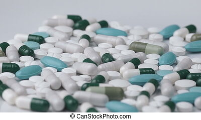 Many pills rotate on a white background