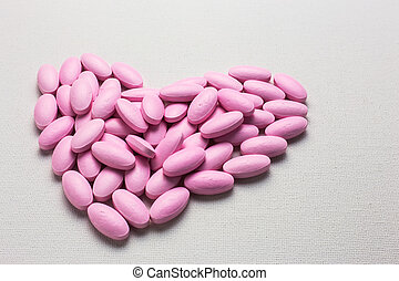 Many pink tablets pills in heart shape