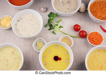 Many plates with different soups on the table