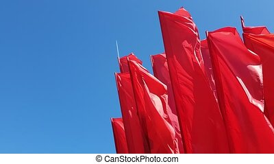 many Red flags swaying in wind against the blue sky - Red...