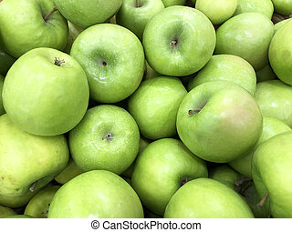 Many ripe green apples lie on the market in a crate