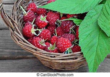 Many Ripe Raspberries With Leafs In Vintage Wicker Basket