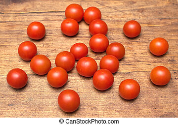Many ripe red tomatoes lies on wood