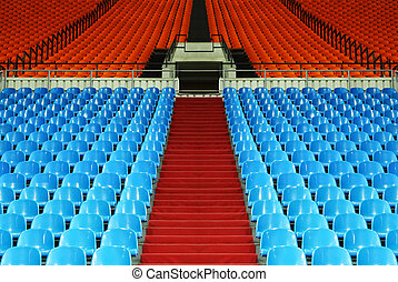 many rows of red and blue empty plastic seats at stadium;...