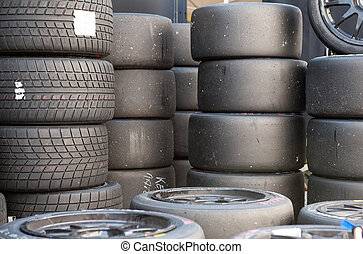 Many sets of motor sport car wet and racing slick tires stacked, new and scratched used