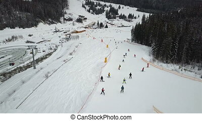 Many skiers and snowboarders descend down the ski slope